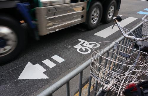 産業道路の自転車通行レーンそばをトラックが