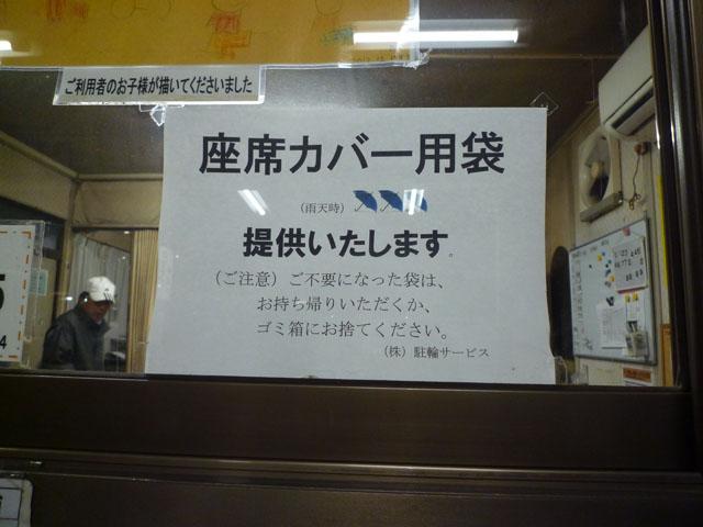 西駅前駐輪場の事務所に貼ってある「座席カバー用袋、提供」とのPOP