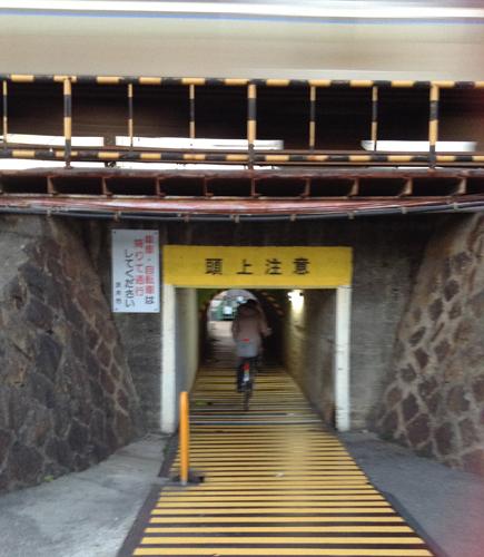 背の低いトンネルを行く人は背をかがめてる